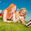Two beautiful girls with notebooks outdoors. Lay on the green gr - Stock Photo