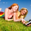 Two beautiful girls with notebook outdoors. Lay on the green gra - Foto de Stock