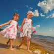 Stock Photo: Two cute sisters play in waves on sea