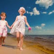 Two cute sisters play in waves on sea — Stock Photo #4711392