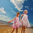 Two cute sisters play in waves on sea - Stock Photo