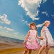 Two cute sisters play in waves on sea — Stock Photo #4711395