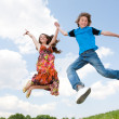 Photo: Girl and boy jumping