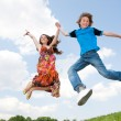 Girl and boy jumping — Stock fotografie #4711540