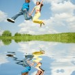 Girl and boy jumping. Reflected in Water - Stok fotoğraf