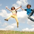 Girl and boy jumping on meadow smiling under blue sky — Stock Photo #4711585