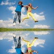 Girl and boy jumping — Stockfoto