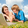 Two Smiling teenagers with laptop resting on meadow. — Stock fotografie