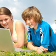 Two Smiling teenagers with laptop resting on meadow. — Stock Photo