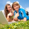 Two Smiling teenagers with laptop resting on meadow. — Stock Photo #4711630
