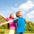 Girl and boy relaxing on meadow smiling under blue sky — Stock Photo #4711641