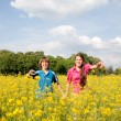Girl and boy relaxing on meadow full of yellow flowers. Soft foc — Stock Photo