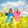 Girl and boy relaxing on meadow full of yellow flowers. Soft foc - Foto Stock