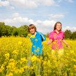 Girl and boy relaxing on meadow full of yellow flowers. Soft foc - Stock Photo