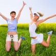 Two beautiful women in white clothes jumping in field — Stock Photo
