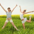 Two young girls are happily jumping on grass — Stock Photo #4711865