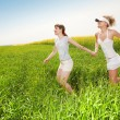 two happy young women are runing in a field — Stock Photo