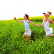 Two happy young women are runing in a field — Stock Photo #4711870