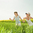Two young girls are happily jumping on grass — Stock Photo
