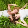 Two beautiful young women lay on green grass outdoors — Stock Photo #4711924