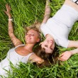 Two beautiful young women lay on the green grass outdoors. — Stock Photo