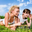 Two beautiful girls in white clothes are laughing and looking at — Stock Photo #4711957