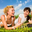 Two beautiful girl in white clothes on a laptop computer outdoor — Stock Photo #4711964