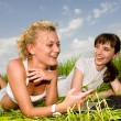 Two beautiful girls in white clothes are laughing near laptop co — Stock Photo #4711965
