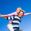 Happy young couple jumping in sky above a green meadow — Stock Photo