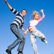 Happy young couple jumping in sky above a green meadow — Stock Photo #4712386