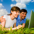 Casual happy couple on a laptop computer outdoors. Lay on the gr — Stock Photo