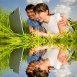 Stock Photo: Happy couple on a laptop computer outdoors. Lay on the green gra