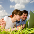 Stock Photo: Casual happy couple on laptop computer outdoors. Lay on gree