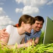 Casual happy couple on laptop computer outdoors. Lay on the gree - Stock Photo