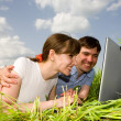 Stock Photo: Casual happy couple on a laptop computer outdoors. Lay on the gr