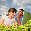 Casual happy couple are talking  and laughing on a laptop comput - Foto Stock