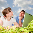 Stock Photo: Casual happy couple on a laptop computer outdoors