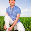 Man is Tying Laces In A Green Field — Stock Photo #4712441