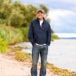 Young smile man on coast of river — Stock Photo