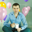 Man with cup in hands against of balloons — Stock Photo