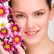 Attractive young woman face with flowers — Stock Photo #4712798