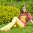 Pretty smiling girl open hands relaxing on green meadow. Soft fo — Stock Photo