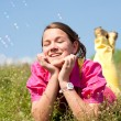Pretty smiling girl relaxing on green meadow full of flowers. So — Stock Photo