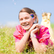 Pretty smiling girl relaxing on green meadow full of flowers. So - Stok fotoğraf
