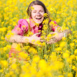 Pretty smiling girl relaxing on green meadow full of yellow flow — Stock Photo
