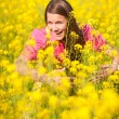Royalty-Free Stock Photo: Pretty smiling girl relaxing on green meadow full of flowers. So