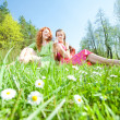 Funny mother and daughter sitting on green grass — Stock Photo #4713057