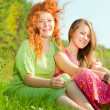 Funny mother and daughter sitting on green grass — Stock Photo #4713070