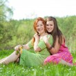 Funny mother and daughter sitting on green grass — Stock Photo #4713091