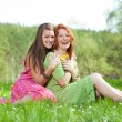 Funny mother and daughter sitting on green grass — Stock Photo